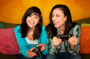 Smiling girl wearing braces playing video game with laughing friend