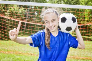 Smiling girl wearing braces and playing soccer