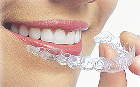 Smiling woman putting in Invisalign aligner