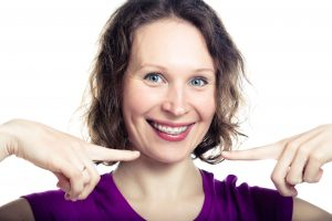 Smiling woman pointing to her braces