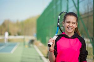 Smiling girl with braces playing tennis