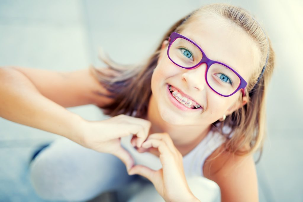 girl with braces holding heart