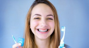 girl with braces smiling with toothbrush