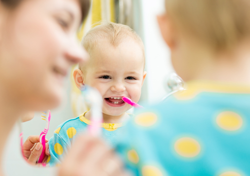 When should my child start using toothpaste and how much should I use?