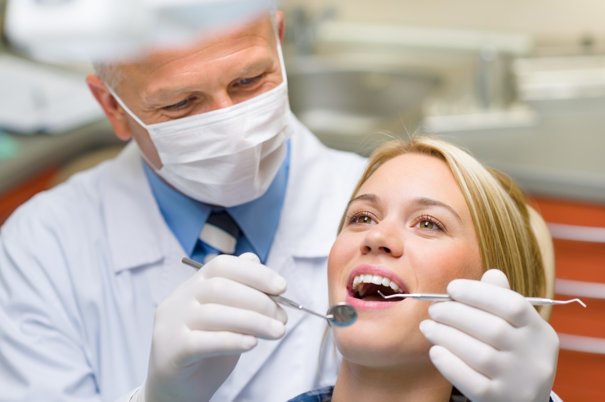 A girl getting her teeth examined at the dentist